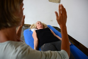 A woman lies on the massage table, she receives a energetical treatment of another woman