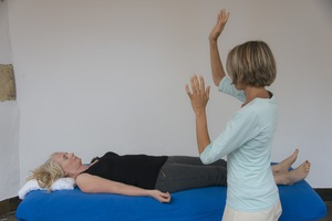 Barbara standing next to her client, who is lying on the massage table. Barbara is giving the spine healing