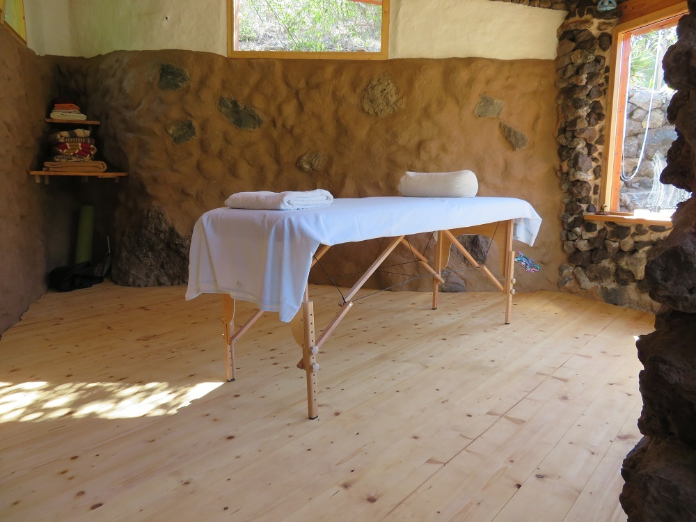 Therapy room made out of natural materials, massage table in the middle of the room