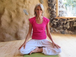 Barbara sitting in meditation pose in a room with woden floor and natural stone and loam walls
